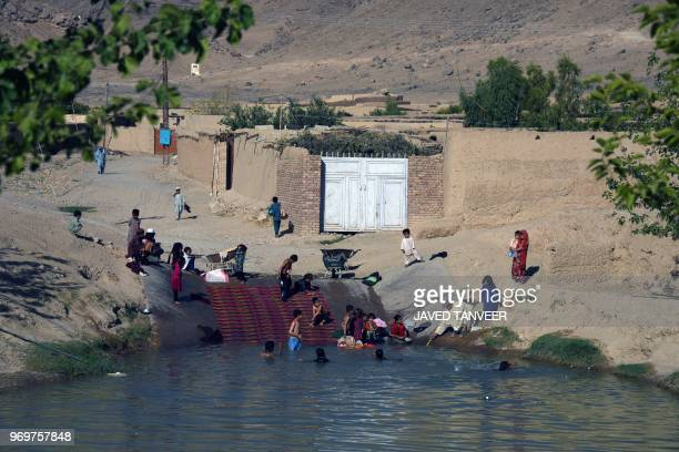 Afghan youth cool down during a hot day at the Zahir Shahi canal in Kandahar province on June 8 2018