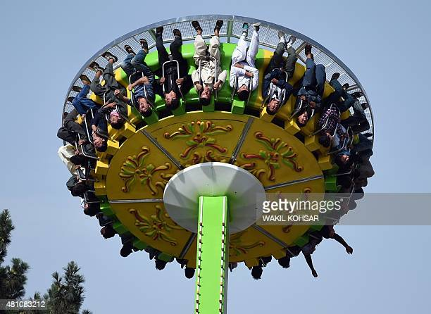 Afghan youth enjoy a ride at a funfair as they celebrate the start of the Eid alFitr holiday which marks the end of Ramadan at the City Park in Kabul...