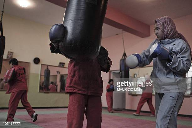 Afghan youth women warm up and hit in a punching ball during a boxing training session at the Olympic Stadium in Kabul on May 17 2010 After years of...