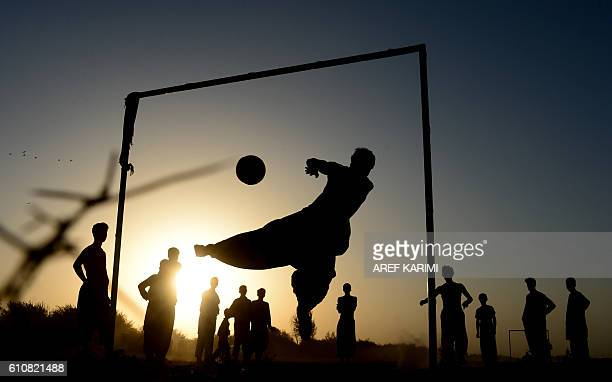 TOPSHOT Afghan youths play football on a field in Herat province on September 28 2016 / AFP / AREF KARIMI
