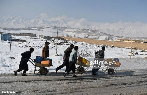 TOPSHOT Afghan youths transport containers of water on wheelbarrows after the first snowfall in Paghman district some 21 km of Kabul on December 15...