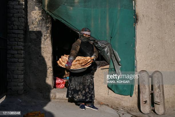 Afghan Zainab Sharifi baker, poses for a photograph holding loaves of bread outside her bakery in Kabul on April 23, 2020 during the COVID-19...
