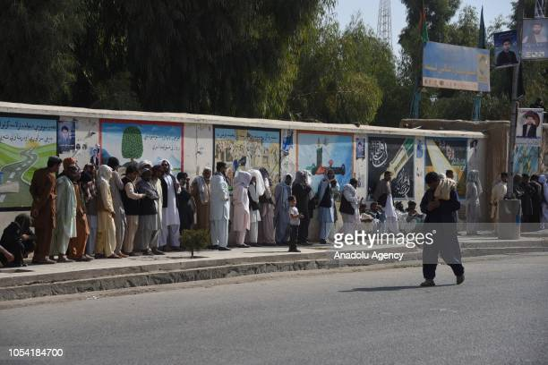 Afghani people wait in the queue before casting their ballots for the parliamentary elections one week later than the rest of the country delayed due...