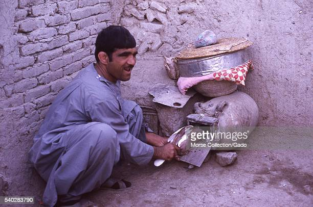 Afghani pigeon seller putting a bird inside a traditional clay jar cage on the floor of his market stall in Kabul, Afghanistan, November, 1973. .