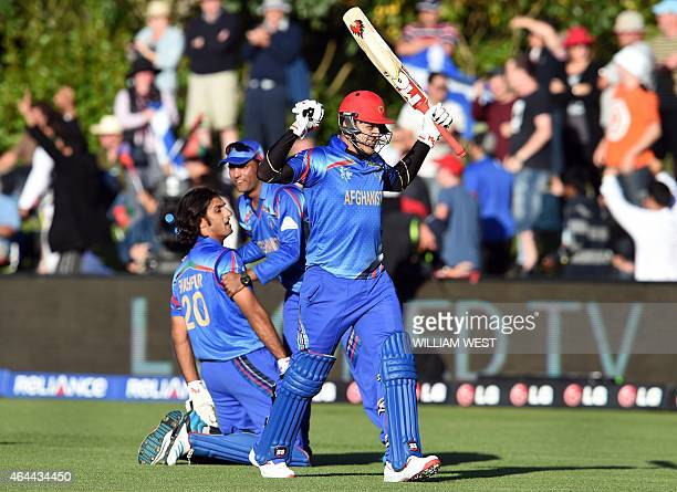 Afghanistan batsman Hamid Hassan celebrates with teammate Shapoor Zadran and reserve Usman Ghani after defeating Scotland in their 2015 Cricket World...
