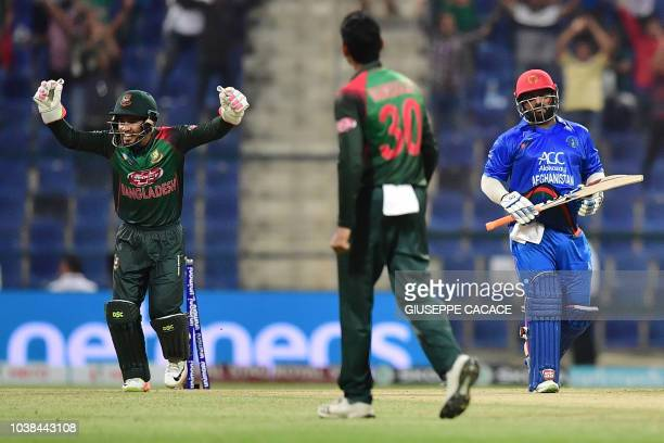 Afghanistan batsman Mohammad Shahzad leaves the pitch after being dismissed during the one day international Asia Cup cricket match between...