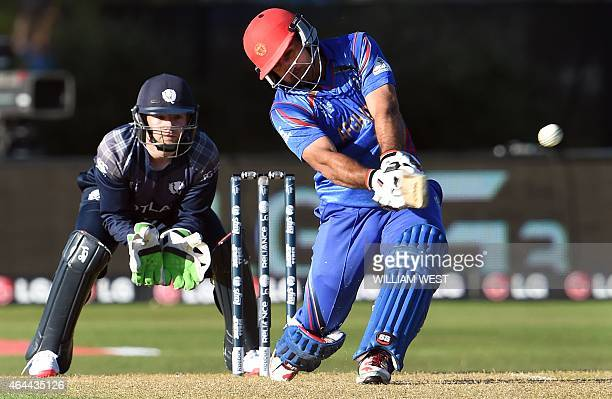 Afghanistan batsman Samiullah Shenwari lofts the ball away to the boundary as Scotland wicketkeeper Matthew Cross looks on during their 2015 Cricket...
