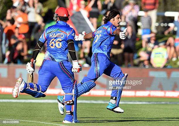 Afghanistan batsman Shapoor Zadran celebrates with teammate Hamid Hassan after hitting the winning runs to defeat Scotland in their 2015 Cricket...