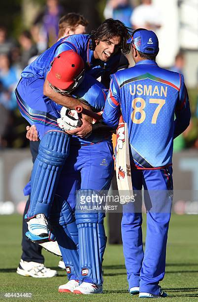 Afghanistan batsman Shapoor Zadran is carried by teammate Hamid Hassan after hitting the winning runs as reserve Usman Ghani looks on after defeating...