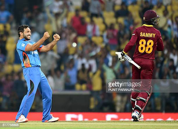 Afghanistan bowler Gulbadin Naib celebrates after taking the wicket of West Indies's batsman Darren Sammy during the World T20 cricket tournament...