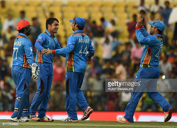 Afghanistan bowler Rashid Khancelebrates with teammates after taking the wicket of West Indies's batsman Marlon Samuels during the World T20 cricket...
