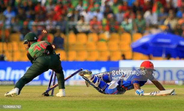 Afghanistan cricketer Hashmatullah Shahidi dives in to complete a run as Bangladesh wicket keeper Liton Das removes the bails during the 6th cricket...
