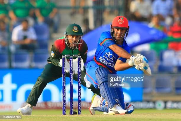 Afghanistan cricketer Hashmatullah Shahidi plays a shot as Bangladesh's wicket keeper Liton Das looks on