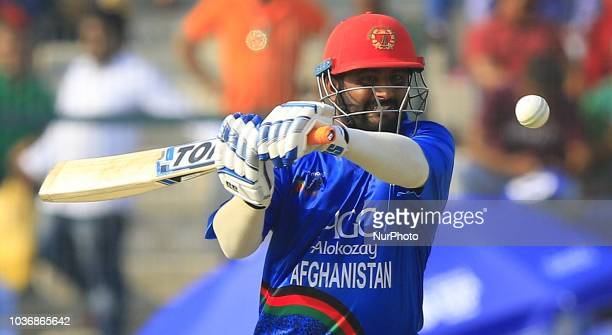 Bangladesh cricketer Abu Hider reacts as Afghanistan cricketers Rashid Khan and Gulbadin Naib congratulate each other during the 6th cricket match of...