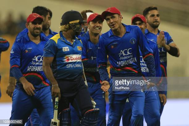 Afghanistan cricketer Mujeeb Ur Rahman and Sri Lankan cricketer Lasith Malinga share a light moment following Sri Lankan cricket teams' loss after...