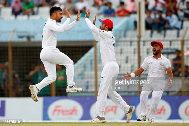 Afghanistan cricketer Rashid Khan celebrates with his teammates after the dismissal of Bangladesh cricketer Musfiqur Rahim during the fourth day of...