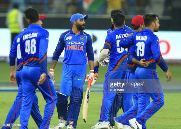 Afghanistan cricketers celebrate after the cricket match ended in a tie during the Asia Cup 2018 cricket match between India and Afghanistan at Dubai...