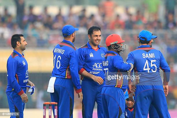 Afghanistan cricketers congratulate Mohammad Nabi after the dismissal of Bangladesh cricketer Shakib Al Hasan during the second One Day International...