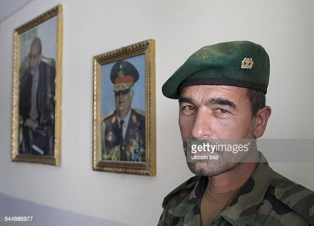 Soldier of the Afghan National Army standing next to the pictures of the defence minister Abdul Rahim Wardak and President Hamid Karzai