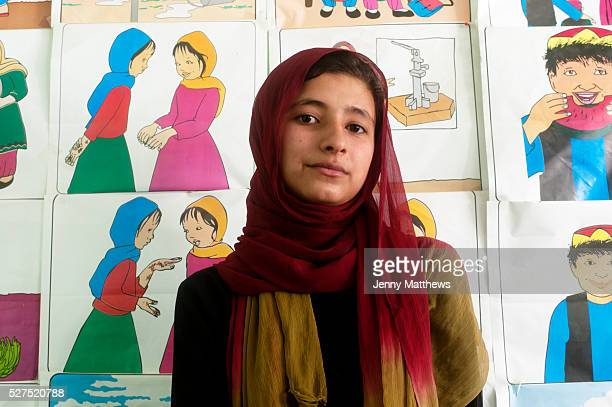 Afghanistan MazareSharif high school Girl aged 14 standing in front of Save the Children posters