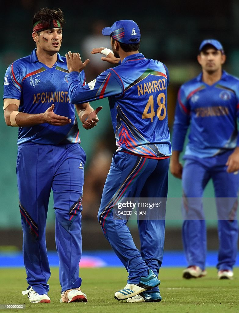 Afghanistan paceman Hamid Hassan (L) celebrates his wicket of England's batsman Alex Hales (not pictured) with teammate Nawroz Mangal during the 2015 Cricket World Cup Pool A match between England and Afghanistan at the Sydney Cricket Ground on March 13, 2015. AFP PHOTO/ Saeed KHAN
