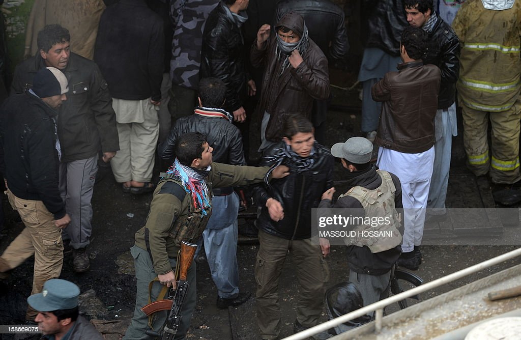 Afghanistan policemen try to move a man from the scene after a huge fire swept through a market in Kabul on December 23, 2012. A huge fire swept through a market in downtown Kabul on December 23, destroying hundreds of shops and forcing the city's nearby money exchange to evacuate, police and witnesses said. There were no reports of any casualties in the early morning blaze which destroyed most of the cloth market's 500 shops, Kabul fire department officials told AFP. AFP PHOTO/ Massoud HOSSAINI