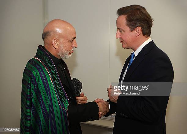 Afghanistan President Hamid Karzai meets with British Prime Minister David Cameron during a bilateral meeting on day two of the NATO Summit at Feira...