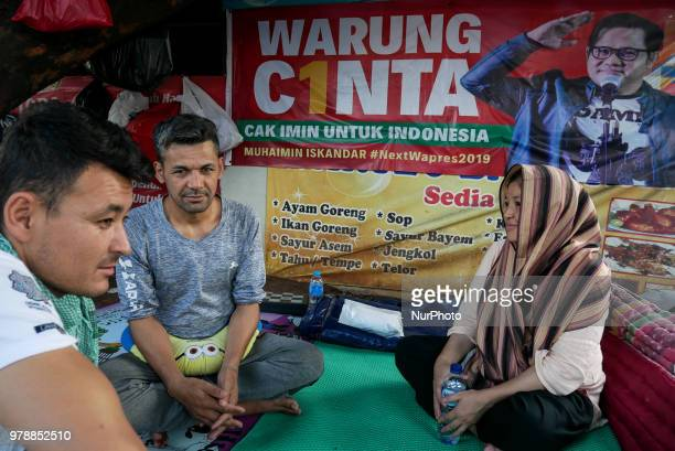 Afghanistan refugees chat as they settling on the roadside in front of the overcapacity immigration detention house in Jakarta Indonesia on June 19...
