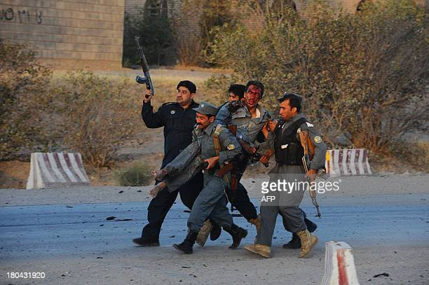 Afghanistan security forces carry a wounded police officer during an attack on the US consulate in Herat on September 13 2013 Gunmen staged an attack...