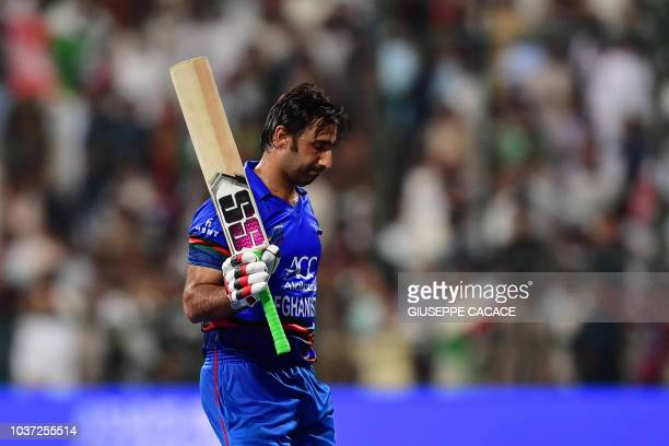 Afghanistan team captain and batsman Mohammad Asghar leaves the pitch after being dismissed during the one day international Asia Cup cricket match...