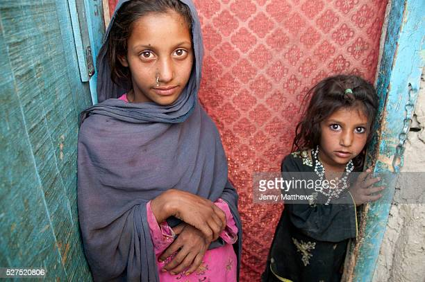 Afghanistan Two girls sisters Ferisha aged 11 and Zahla Bibi aged 6 stand in a doorway Charahi Spinkali district 5 Kabul