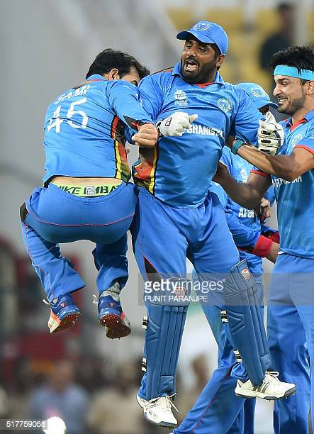 Afghanistan' wicketkeeper Mohammad Shahzadcelebrates with teammates after the wicket of West Indies's batsman Andre Russell during the World T20...