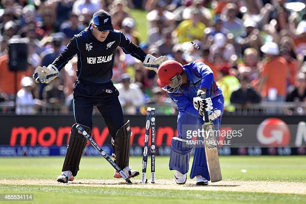 Afghanistan's batsman Usman Ghani is bowled by New Zealand bowler Daniel Vettori as New Zealand wicketkeeper Luke Ronchi looks on during the Pool A...