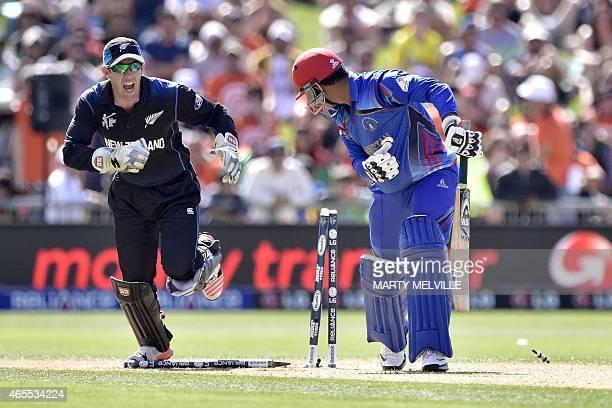 Afghanistan's batsman Usman Ghani is bowled by New Zealand bowler Daniel Vettori as New Zealand wicketkeeper Luke Ronchi celebrates during the Pool A...