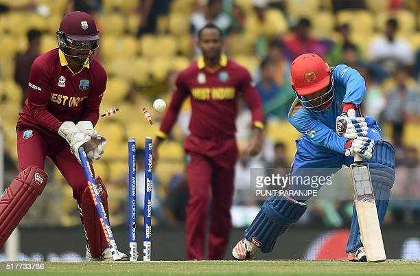 Afghanistan's batsman Usman Ghaniis watched by West Indies's Denesh Ramdin as he is bowled during the World T20 cricket tournament match between West...