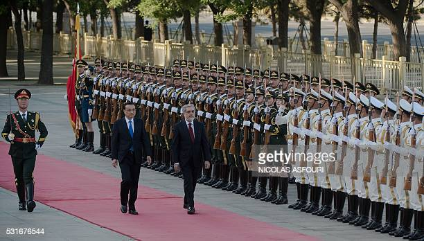 Afghanistan's Chief Executive Officer Abdullah Abdullah reviews a military honour guard with Chinese Premier Li Keqiang during a welcome ceremony in...