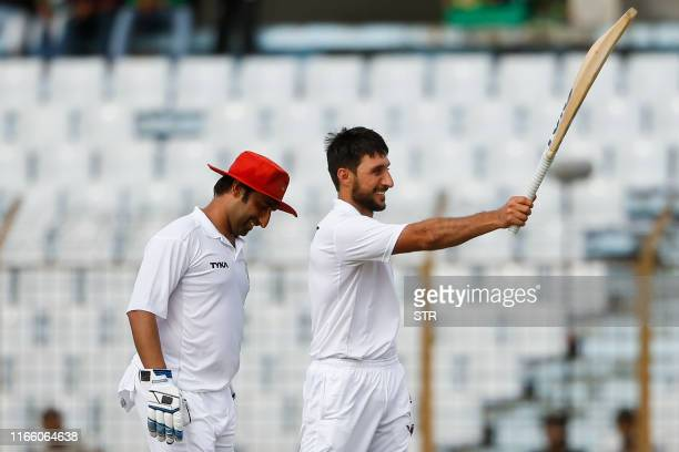 Afghanistan's cricketer Rahman Shah raises his bat to celebrate scoring a century during the first day of the one-off cricket Test match between...