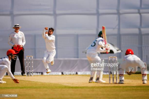 Afghanistan's cricketer Rashid Khan delivers a ball during the second day of the oneoff cricket Test match between Bangladesh and Afghanistan at the...