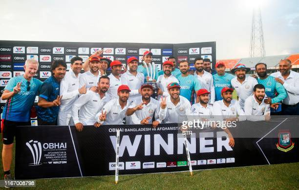 Afghanistan's cricketers and team members pose with their winning trophy after defeating Bangladesh in the oneoff cricket Test match at Zohur Ahmed...