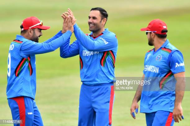 Afghanistan's Mohammad Nabi celebrates with Afghanistan's Najibullah Zadran after taking the wicket of Pakistan's Shoaib Malik for 44 runs during the...