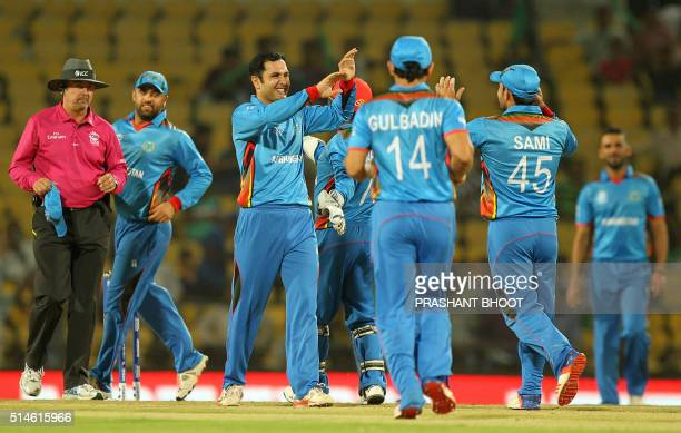 Afghanistan's Mohammad Nabicelebrates with teammates after the dismissal of unseen Hong Kong batsman Ryan Campbell during the World T20 cricket...
