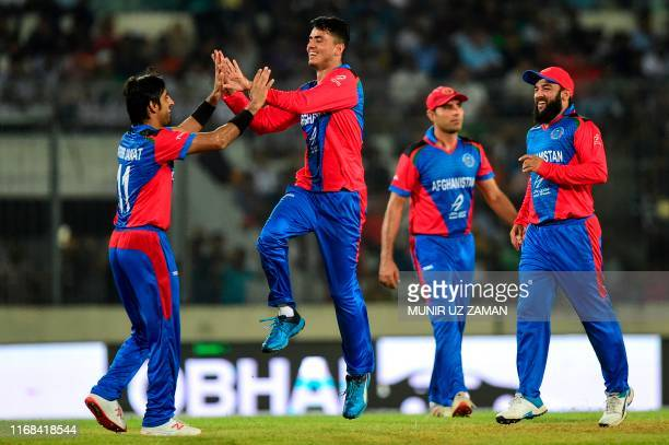 Afghanistan's Mujeeb Ur Rahman celebrates with his teammates after the dismissal of Bangladesh's Soumya Sarkar during the third match between...