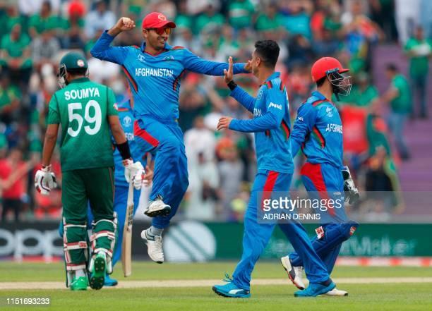 TOPSHOT Afghanistan's Mujeeb Ur Rahman celebrates with teammate Afghanistan's Mohammad Nabi after the dismissal of Bangladesh's Soumya Sarkar during...