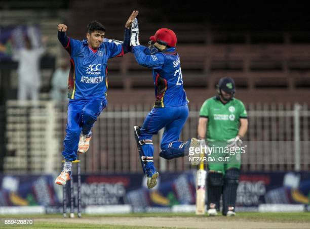 Afghanistan's Mujeeb Zadran celebrates the wicket of Ireland's William Porterfield during the third one day international cricket match between...