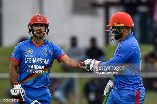 Afghanistan's Najibullah Zadran and teammate Samiullah Shinwari touch their gloves during the first T20 cricket match between Afghanistan and Ireland...