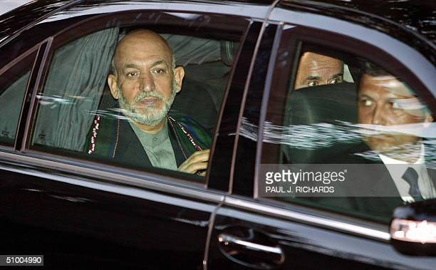 Afghanistan's Presidend Hamid Karzai sits patiently in his armored car as his security staff looks about on his arrival for a State dinner at Topkapi...