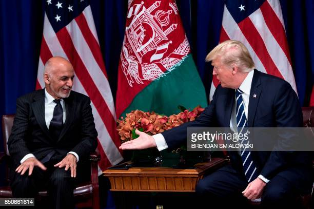 TOPSHOT Afghanistan's President Ashraf Ghani and US President Donald Trump shake hands before a meeting at the Palace Hotel during the 72nd United...