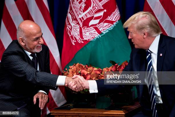 Afghanistan's President Ashraf Ghani and US President Donald Trump shake hands before a meeting at the Palace Hotel during the 72nd United Nations...