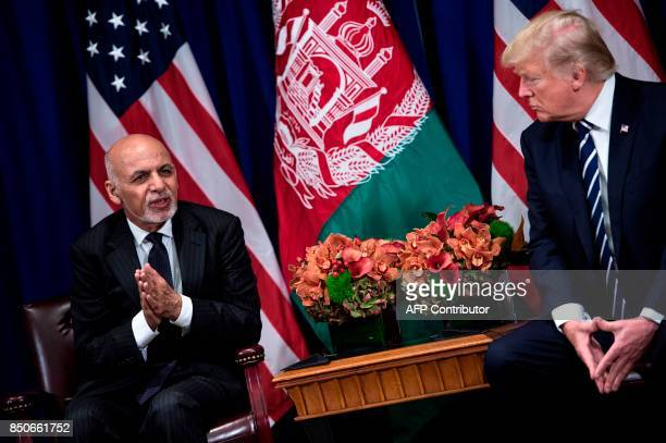Afghanistan's President Ashraf Ghani makes a statement for the press as US President Donald Trump listens before a meeting at the Palace Hotel during...