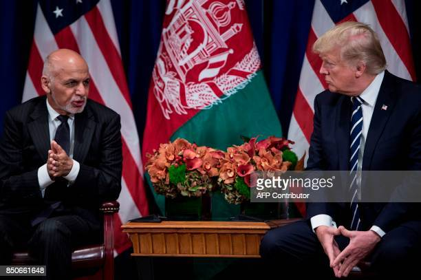 Afghanistan's President Ashraf Ghani speaks as US President Donald Trump listens before a meeting at the Palace Hotel during the 72nd United Nations...